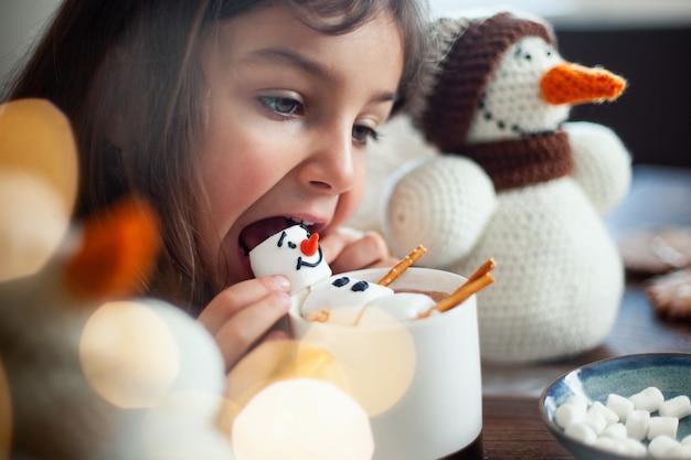 La bambina carina mangia un pupazzo di neve di marmmello decorato con glassa e beve cacao