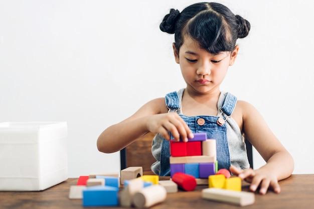 La piccola ragazza sveglia gode di mentre gioca i giocattoli di legno dei blocchi sulla tavola a casa