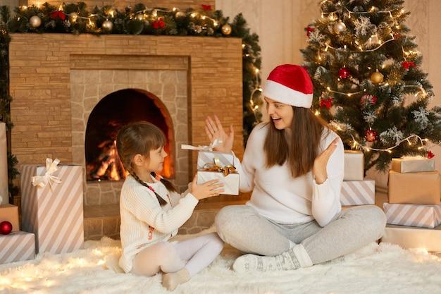 Piccola ragazza carina che dà presente a sua madre, donna eccitata che ottiene confezione regalo, famiglia seduta sul pavimento sul morbido tappeto vicino al camino e albero di natale decorato.