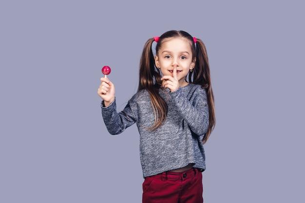 La piccola ragazza carina tiene in mano il lecca-lecca rosso e mostra shh. isolato su superficie grigia