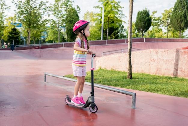 Bambina carina che impara a guidare uno scooter in un parco cittadino in una giornata di sole estivo