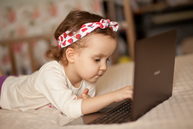 Piccola ragazza sveglia in una maschera medica che si trova sul letto e che per mezzo di un taccuino digitale del computer portatile della compressa. chiamate online amici o genitori.