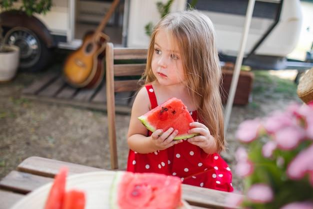 Piccola ragazza sveglia su un picnic con l'anguria
