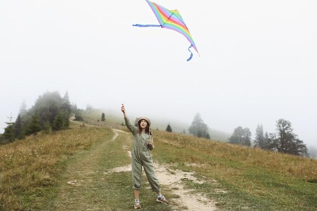 Piccola ragazza carina che gioca con l'aquilone colorato in una giornata nebbiosa in montagna. bambino felice in tuta verde e berretto si diverte all'aria aperta