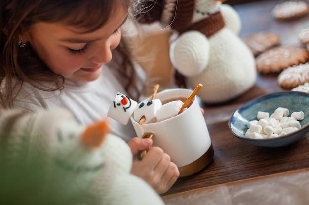 Una bambina carina gioca con pupazzi di neve a maglia e mangia pan di zenzero e beve cacao con marshmallow
