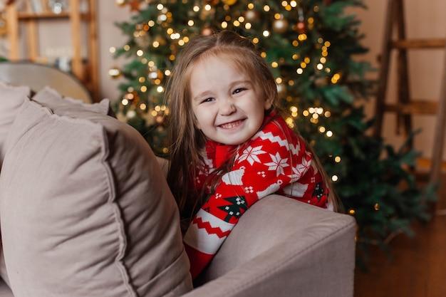 La piccola ragazza sveglia in maglione rosso di natale gioca dall'albero di natale a casa. decorazione di capodanno.