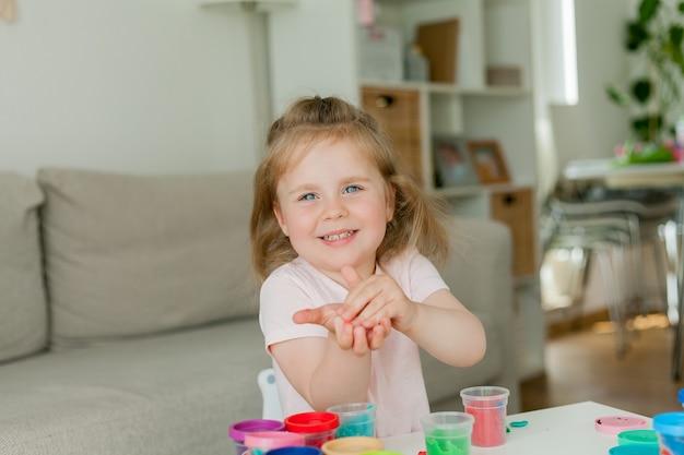 Bambina carina scolpisce dalla plastilina colorata.
