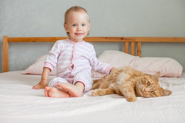 Una ragazzina carina si siede sul letto con un grasso gatto allo zenzero che accarezza e gioca con lui