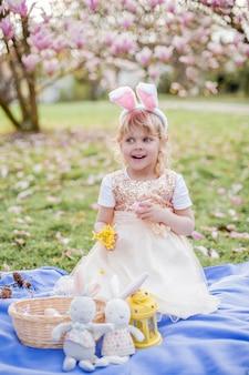 Piccola ragazza carina che si siede sull'erba vicino alla magnolia. una ragazza vestita da coniglietto pasquale tiene in mano un fiore e un uovo. primavera.