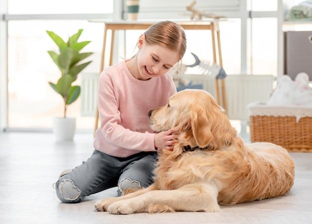 Piccola ragazza carina seduta con il sorriso sul suo viso sul pavimento e accarezzare il cane golden retriever