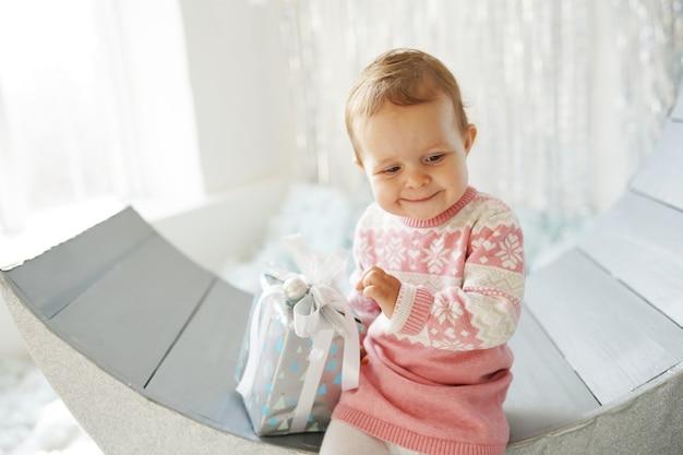 Piccola ragazza sveglia nel maglione che tiene scatola regalo di natale