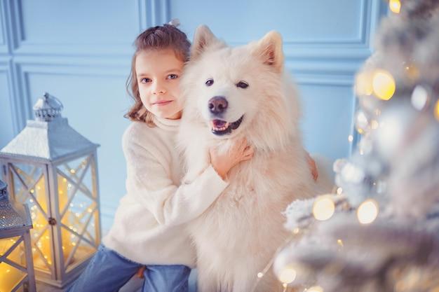 Bambina carina con un cane malamute bianco vicino all'albero di natale.