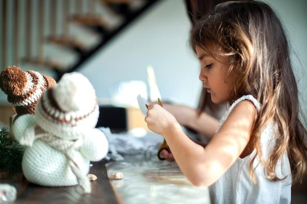 La piccola ragazza carina e la giovane bella donna hanno tagliato i fiocchi di neve da carta bianca. pan di zenzero e cacao con marshmallow. il concetto di preparazione per il nuovo anno e il natale.