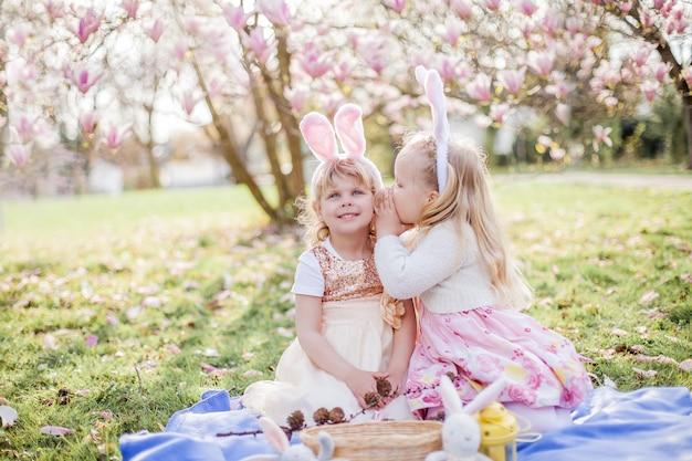 Piccole ragazze carine sono sedute sull'erba vicino alla mogolia. ragazze in costume coniglietti pasquali. primavera.