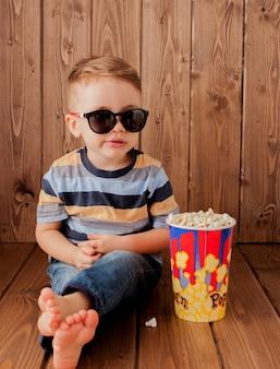 Piccolo bambino sveglio del bambino 2-3 anni, vetri del cinema di imax 3d che tiene secchio per popcorn, mangiare fast food su fondo di legno. concetto di stile di vita infanzia bambini. copia spazio.