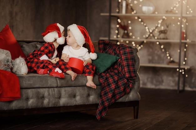 Piccoli bambini carini in cappelli di babbo natale seduto su una grande sedia accogliente in camera con scatola di regali di natale
