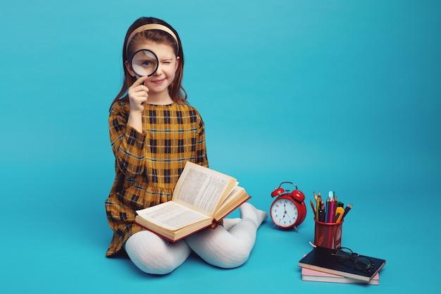Piccola studentessa carina in abito a scacchi con lente d'ingrandimento e sorridente