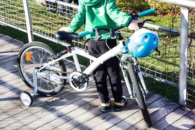 Piccolo ciclista a passeggio. il ragazzo padroneggia la bicicletta. intenzioni serie nel ciclismo. imparare ad andare in bicicletta. la ricerca dello sport.