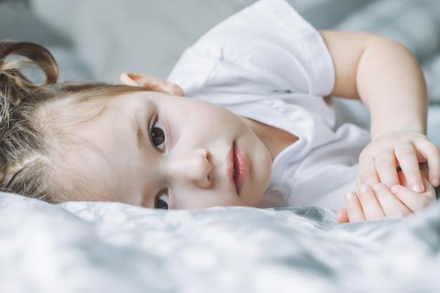 La piccola ragazza dai capelli scuri 24 con due code di cavallo giace su un fianco sul letto e guarda nella cornice
