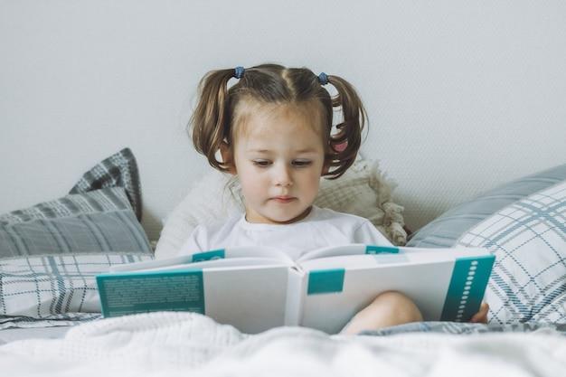 La piccola ragazza dai capelli scuri 24 con due code di cavallo si siede sul letto con cuscini e legge il libro