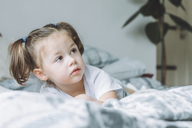 La piccola ragazza dai capelli scuri con due code di cavallo si trova sul letto a pancia in giù