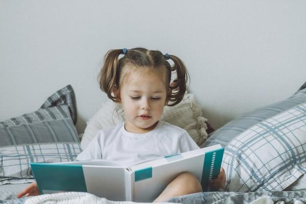 La piccola ragazza dai capelli scuri con due code di cavallo si siede sul letto con cuscini e legge il libro