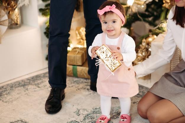 La piccola figlia in abiti carini si rallegra e sorride nell'atmosfera del nuovo anno