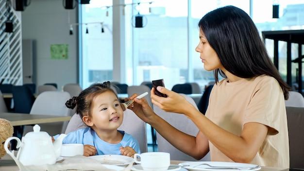 La piccola figlia aiuta la mamma ad applicare il trucco, primo piano