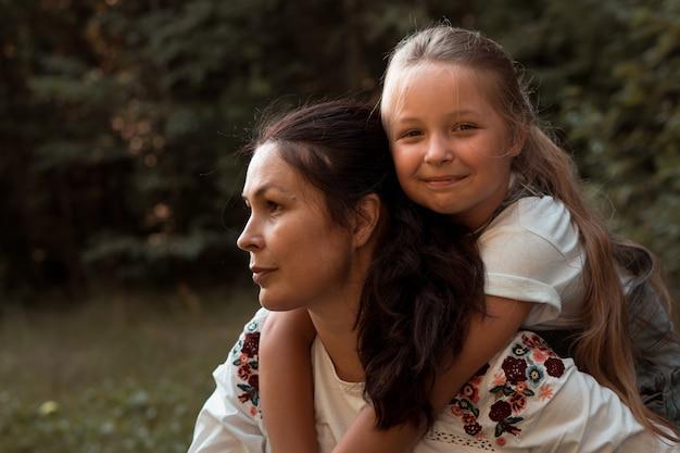 Piccola figlia che abbraccia la madre nel parco in estate