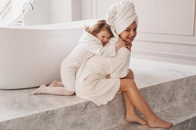 La piccola figlia abbraccia mamma, madre e figlia in camice bianco in bagno luminoso