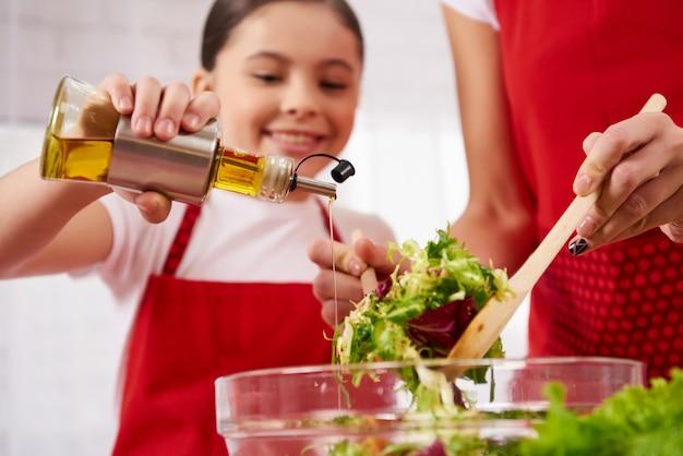 La piccola figlia versa l'olio d'oliva in insalata sulla cucina.