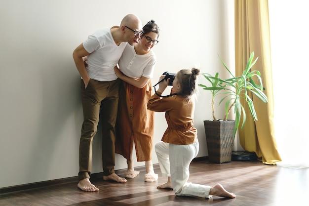 Piccola figlia che fotografa i suoi genitori. che sono in posa davanti a una macchina fotografica.