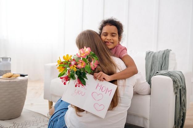 La piccola figlia augura buon compleanno alla sua amata madre in soggiorno living