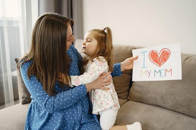 Piccola figlia con coda di cavallo. mamma incinta in un vestito. figlia con una foto.