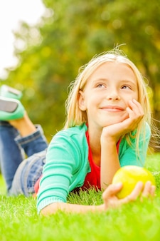 Piccolo sognatore diurno. bambina sveglia che si appoggia la testa a portata di mano e distoglie lo sguardo con un sorriso mentre giace sull'erba verde
