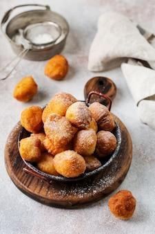 Piccole ciambelle. ricotta fatta in casa biscotti fritti in grasso profondo e cosparsi di zucchero a velo in un piatto vintage
