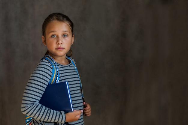 Piccola ragazza della scuola europea con zaino e libri