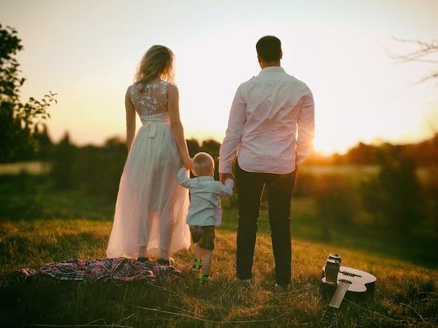 Piccola scena di picnic romantico in famiglia all'aperto al tramonto genitori che si tengono per mano di un bambino piccolo