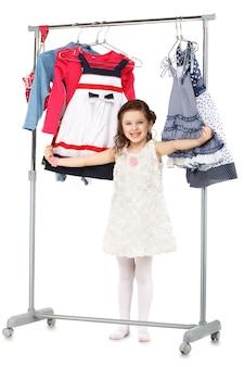La piccola ragazza alla moda sceglie i vestiti in un armadio isolato su bianco