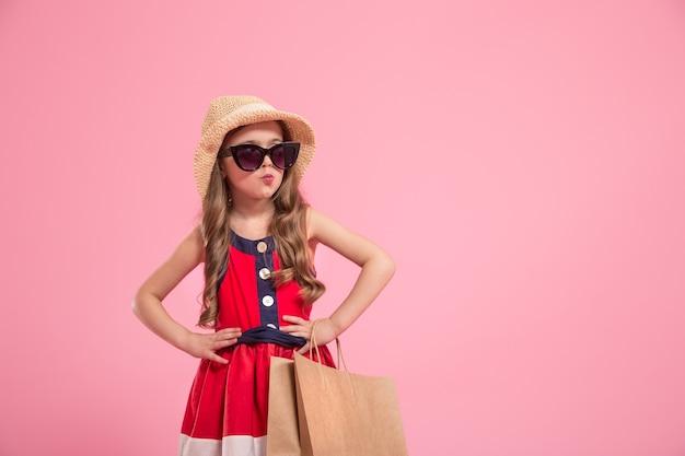 Piccola fashionista con una borsa della spesa in cappello estivo e occhiali da sole, sfondo rosa colorato, il concetto di moda per bambini