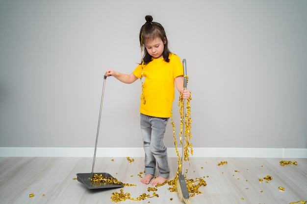 Piccolo bambino femmina pulizia soggiorno con scopa a casa. ragazza triste che tiene paletta e frusta.