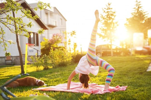 Piccola ragazza flessibile che esegue ginnastica su una coperta sull'erba mentre il suo cane la sta guardando.