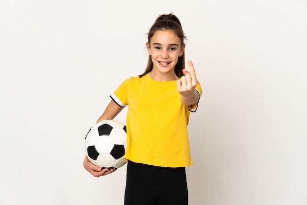 Piccola ragazza del giocatore di football isolata su fondo bianco che fa il gesto venente