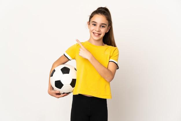 Piccola ragazza del giocatore di football isolata su fondo bianco che indica il lato per presentare un prodotto