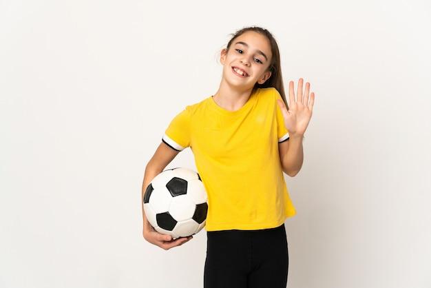 Piccola ragazza del giocatore di football americano isolata su priorità bassa bianca che saluta con la mano con l'espressione felice