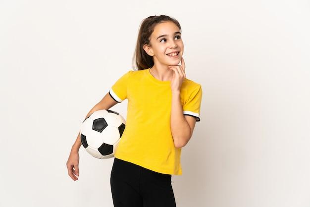 Piccola ragazza del giocatore di football americano isolata sulla parete bianca che pensa un'idea mentre osserva in su