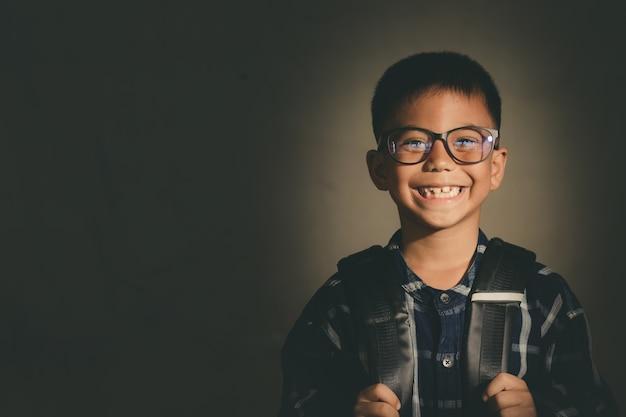Piccolo ragazzo straniero, studente, bambino in possesso di sorrisi borsa scuola con divertimento e felice, vintage
