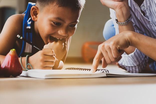 Piccolo ragazzo straniero, studente, bambino sorride, apprende con divertimento e felicità nel classro