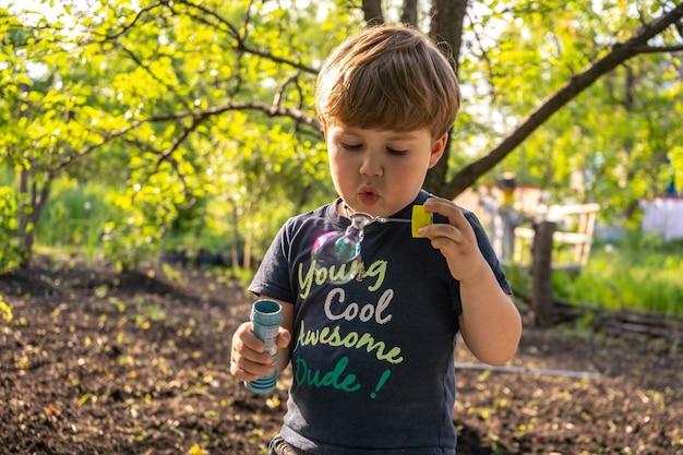 Piccolo ragazzo di quattro anni fa bolle di sapone, all'aperto, estate, ragazzo felice