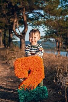 Piccolo bambino divertente con il numero due in natura.